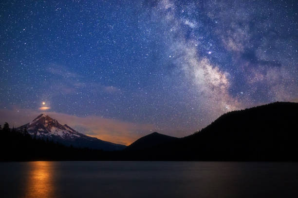 Starry night sky with Mars rising over Mt. Hood from Lost Lake, Oregon, USA. Starry night sky with Mars and the Milky Way rising over Mt. Hood from Lost Lake, Oregon, USA. The reflection of Mars is visible in the lake water below the mountain. mt hood stock pictures, royalty-free photos & images