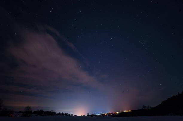 starry sky with small clouds over the city in the distance - céu a noite imagens e fotografias de stock