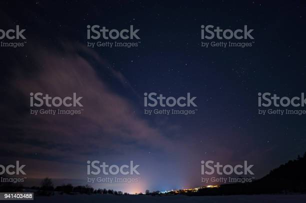 Photo of Starry sky with small clouds over the city in the distance