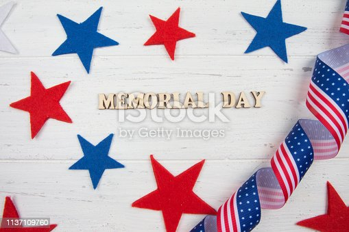 971061452istockphoto Stars and American flag. Memorial Day. White wooden background 1137109760