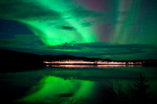 Stars and Northern Lights over dark Road at Lake