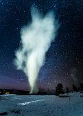 Old Faithful geyser at dusk in Yellowstone National Park