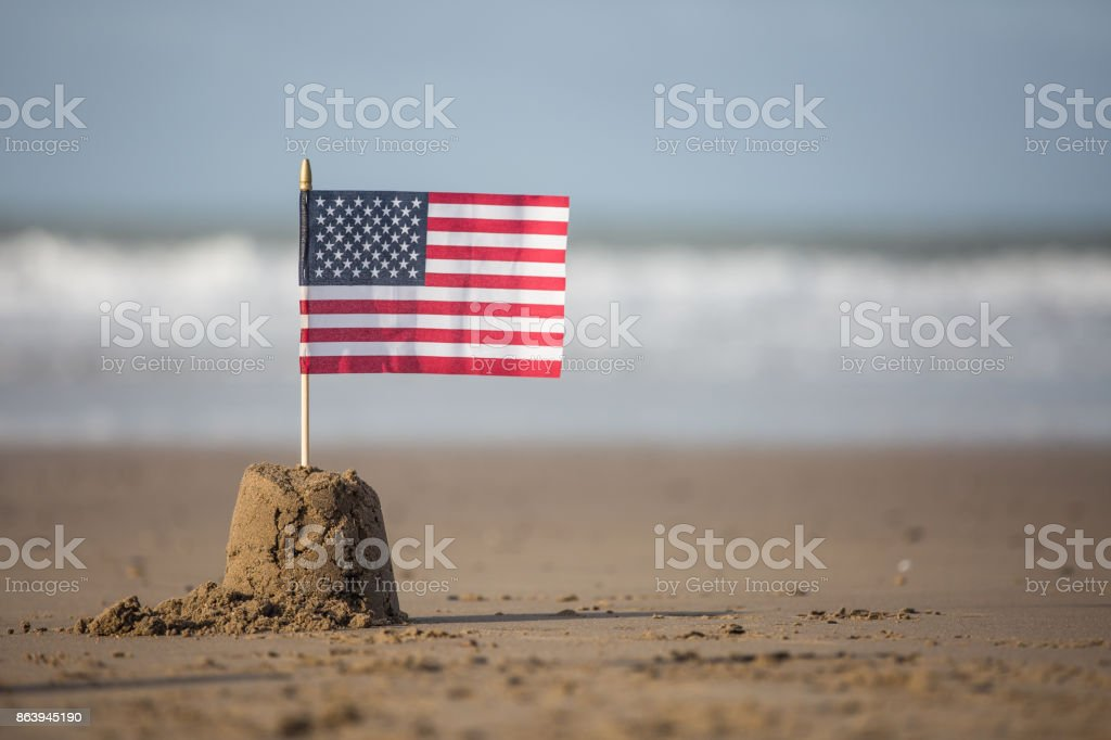 USA stars and stripes flag flying from a sandcastle stock photo