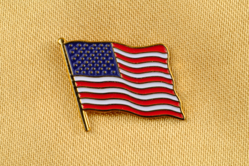 Stars and Stripes Flag Pin on gold satin background.