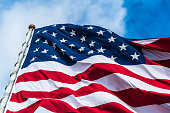 Stars and Stripes on American Flag with clouds passing in the background close up on the top corner of the flag