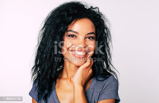 910856488 istock photo Stars in my eyes. Alluring African ethnic girl with broad sincere smile and mesmerizing dark eyes is looking to the camera and smiling broadly while touching her neck with her left hand. 1180642197