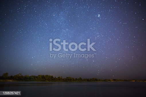 971578384 istock photo Stars on dark background. Summer night sky with stars. Beautiful natural background. Mystical landscape. Beautiful starry sky. Long exposure night photography. Bright stars reflected on river surface 1205257421