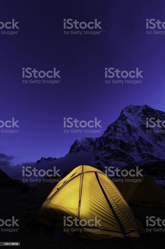 Chrome blue starry skies over the snow capped peaks glowing in the...