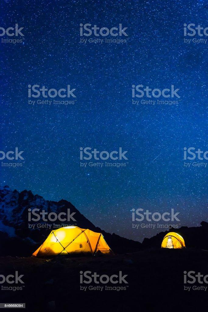 Stars shining night sky over illuminated mountain tents Himalayas Nepal stock photo