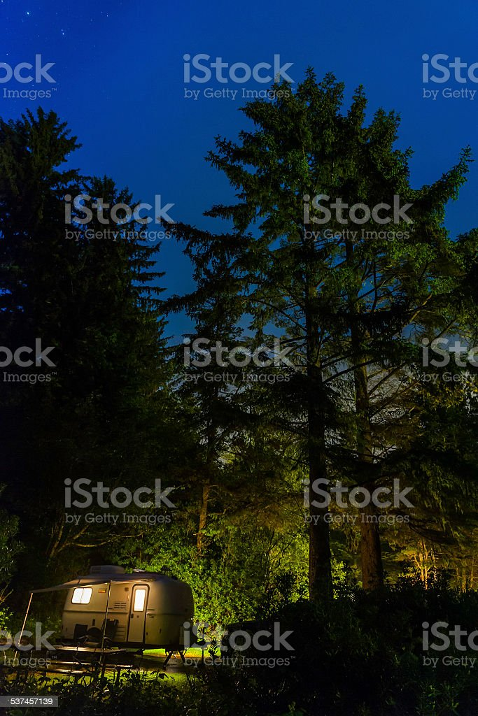 Stars shining over illuminated trailer forest campsite Pacific Northwest USA stock photo