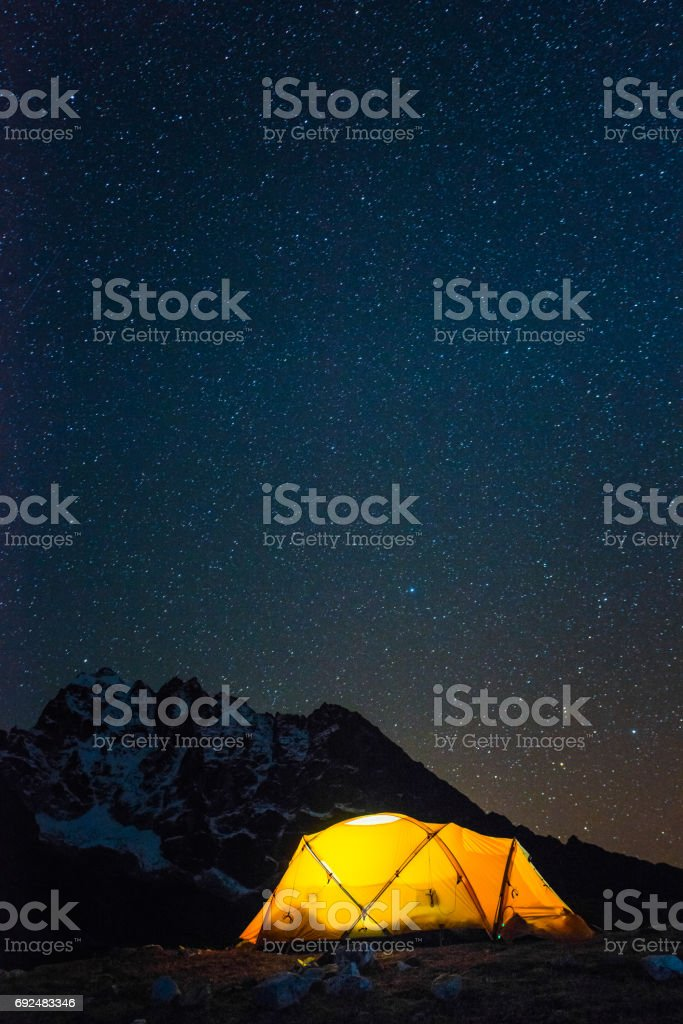 Stars shining over warmly illuminated camping tent Himalaya mountains Nepal stock photo