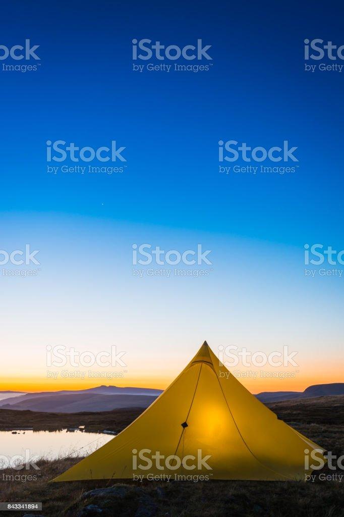 Stars shining over yellow tent camping beside mountain lake sunrise stock photo