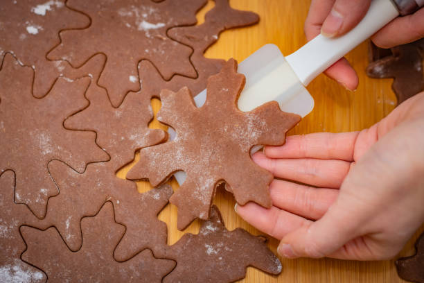 Star-shaped cake is lifted by a woman's hands with a white spatula, the preparation for Christmas pastries – zdjęcie