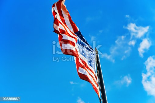 istock Star-striped American flag flutters proudly against the blue sky. 993359862
