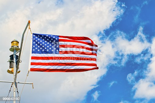 istock Star-striped American flag flutters proudly against the blue sky. 996640192