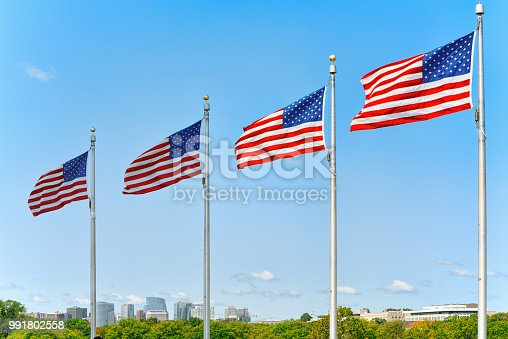 istock Star-striped American flags flutters proudly against the blue sky near  Washington Memorial. 991802558