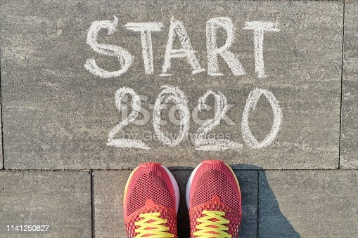 istock Start 2020, text on gray sidewalk with woman legs in sneakers, top view 1141250827