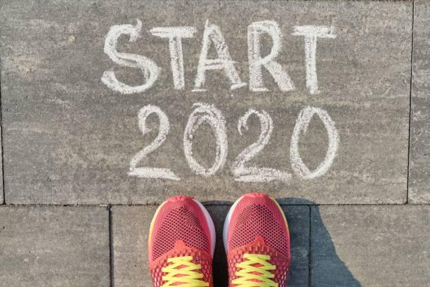 start 2020, text på grå trottoaren med kvinno ben i sneakers, uppifrån - calendar workout bildbanksfoton och bilder