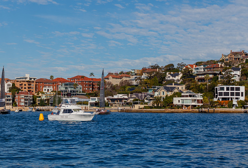 Sydney, NSW, Australia. July 19, 2020: Start boat during the winter series from Cruising Yacht Club of Australia, with Double Bay homes in the background
