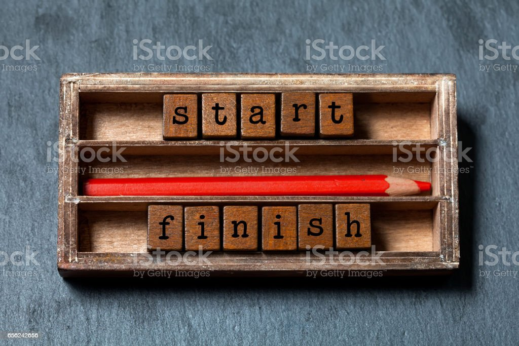 Start finish concept. Vintage box, wooden cubes phrase with old style letter, red pencil. Gray stone textured background. Close-up, up view, soft focus stock photo