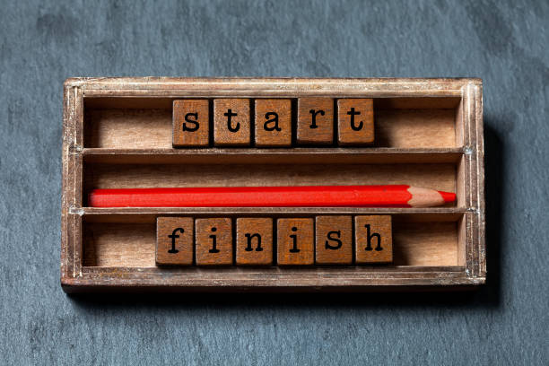 Start finish concept. Vintage box, wooden cubes phrase with old style letter, red pencil. Gray stone textured background. Close-up, up view, soft focus – Foto