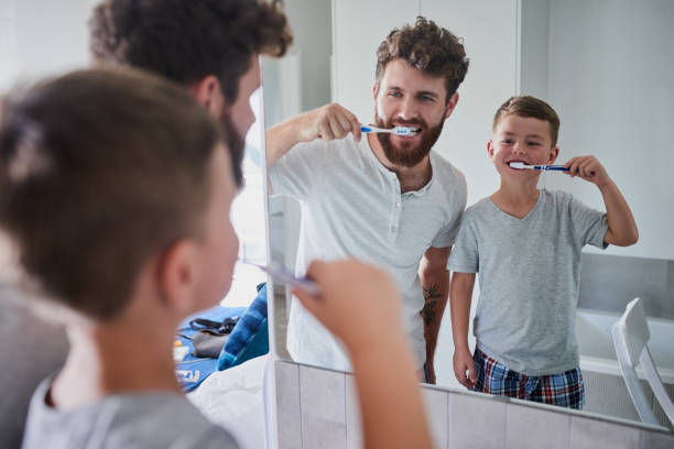 Start good oral habits early Shot of a father and his little son brushing their teeth together in the bathroom at home dental health stock pictures, royalty-free photos & images