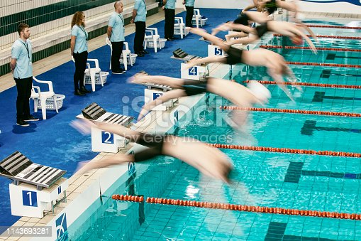 Freestyle stroke swimming competition start for men at a swimming tournament. Referees at the side of a swimming pool.