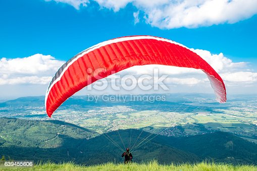 Paraglider in starting phase in front of the mountains.