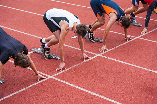 Start of the race Sprinters in starting blocks just starting the race. Side shot. Running track series. track starting block stock pictures, royalty-free photos & images