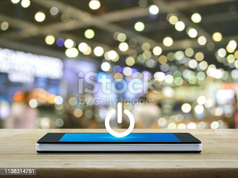 Power button icon on modern smart phone screen on wooden table over blur light and shadow of shopping mall, Start up business concept