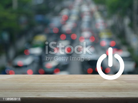 Power button flat icon over blur of rush hour with cars and road in city, Start up business concept