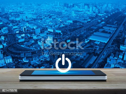 Power button icon on modern smart phone screen on wooden table over city tower, street and expressway, Start up business concept