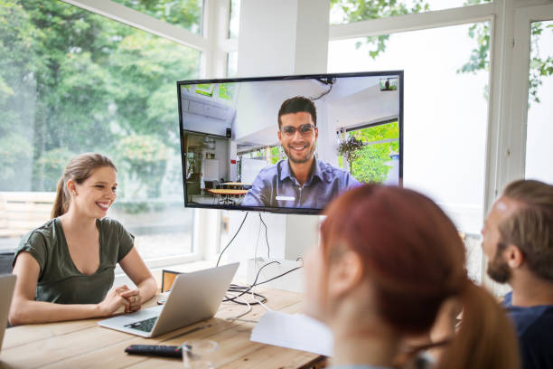 Start up business group having a video conference Businesswoman discussing with colleagues during video conference. Start up business group having a video conference in new office boardroom. leisure equipment stock pictures, royalty-free photos & images