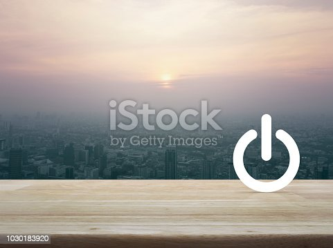 Power button icon over aerial view of cityscape at sunset, vintage style, Start up business or industry concept