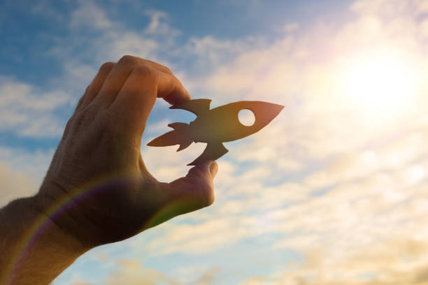Start up concept. Rocket in the hand of a businessman against the sky in the rays of the sun. stock photo