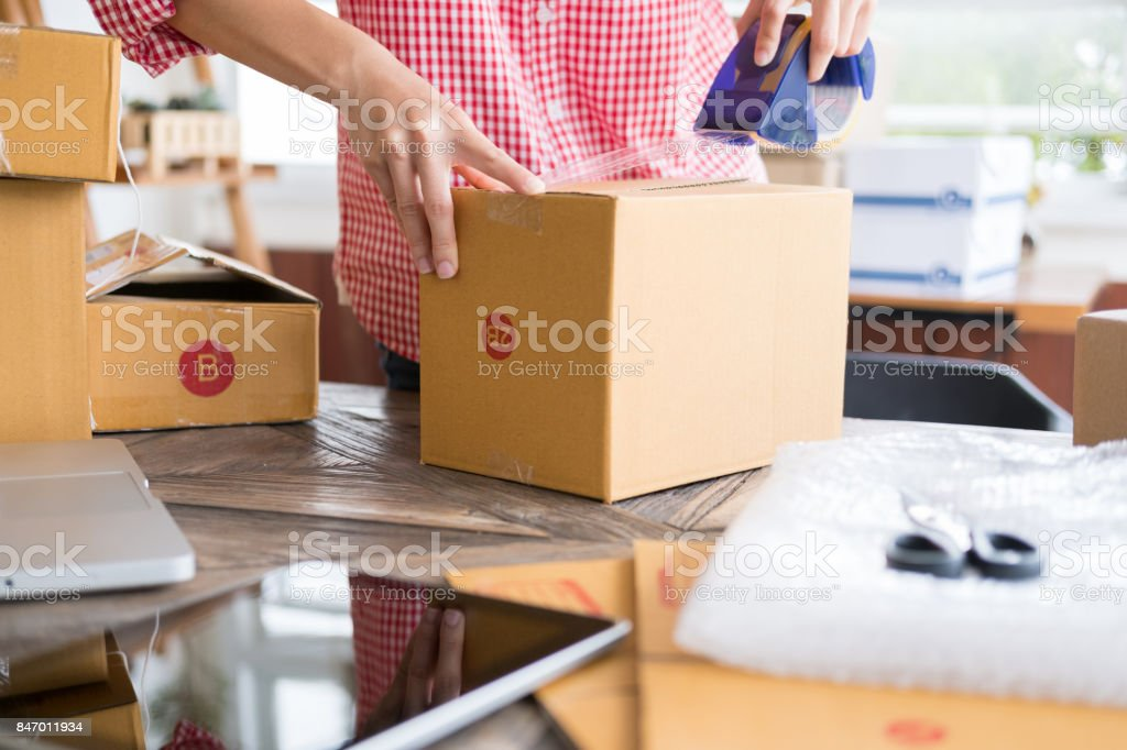 start up small business owner packing cardboard box at workplace. freelance woman entrepreneur SME seller prepare parcel box of product for deliver to customer.  Online selling, internet marketing, e-commerce, shipping concept stock photo