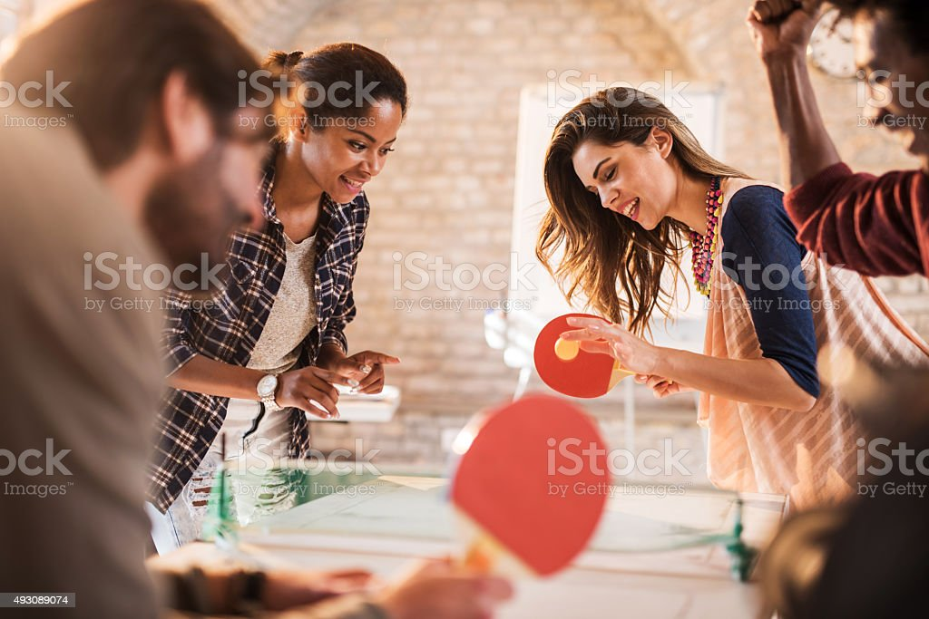 Start up team having fun while playing table tennis. stock photo