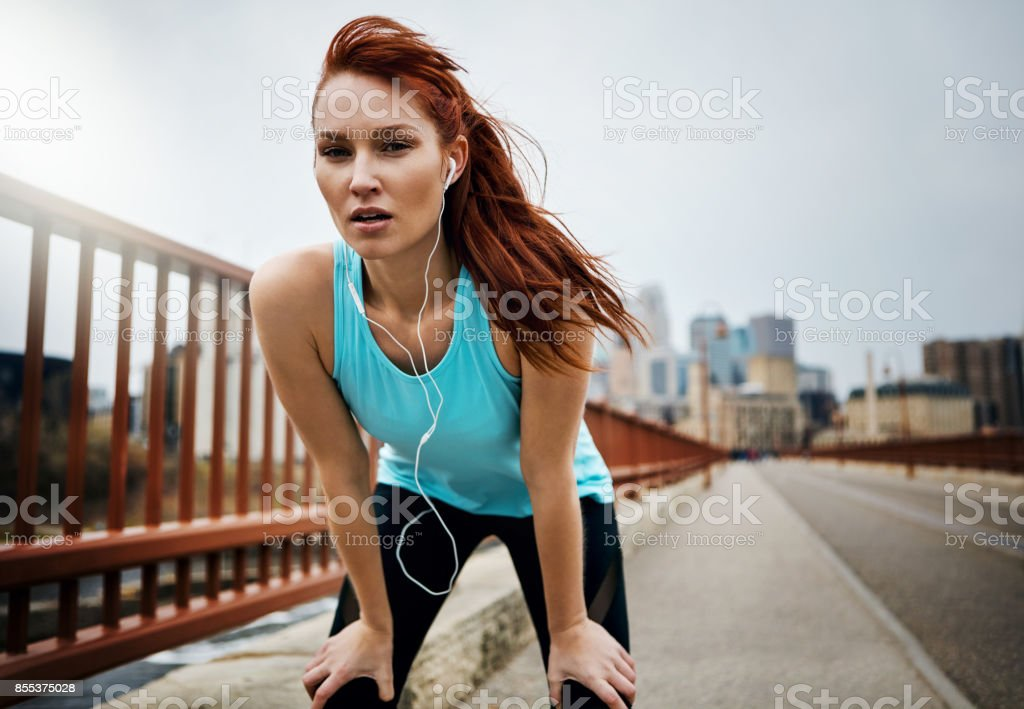 Portrait of a sporty young woman taking a break while running in the...