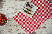 Directly above of wooden table with picnic tablecloth, a plate with sweet food, and part of a big bowl of strawberries.