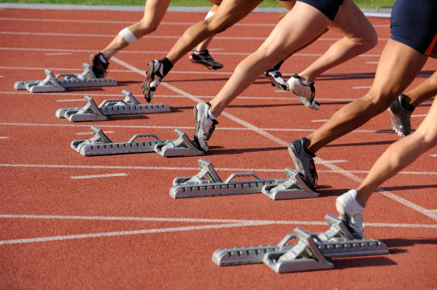 Starting Block The start of the woman's 100 meter dash at a college track meet. track starting block stock pictures, royalty-free photos & images