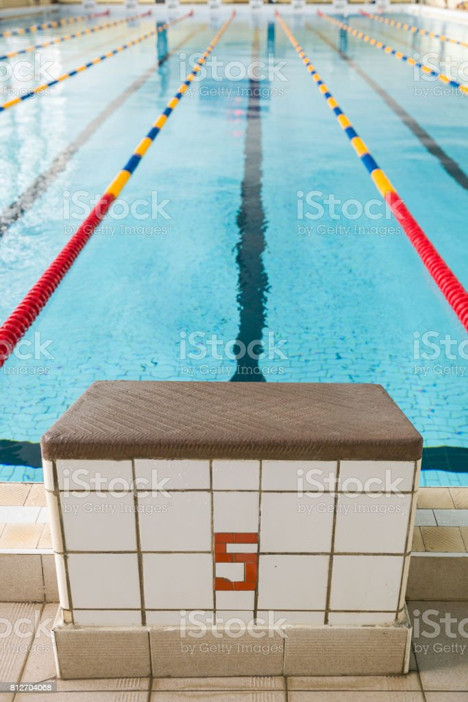 Starting blocks and lanes in a swimming pool. Edge of indoors sport swimming pool. Starting platforms with number 5 for swimming races and competitions. Sport and health concept stock photo