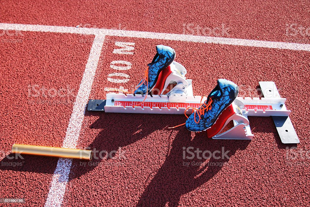 Starting blocks with spikes and a baton stock photo