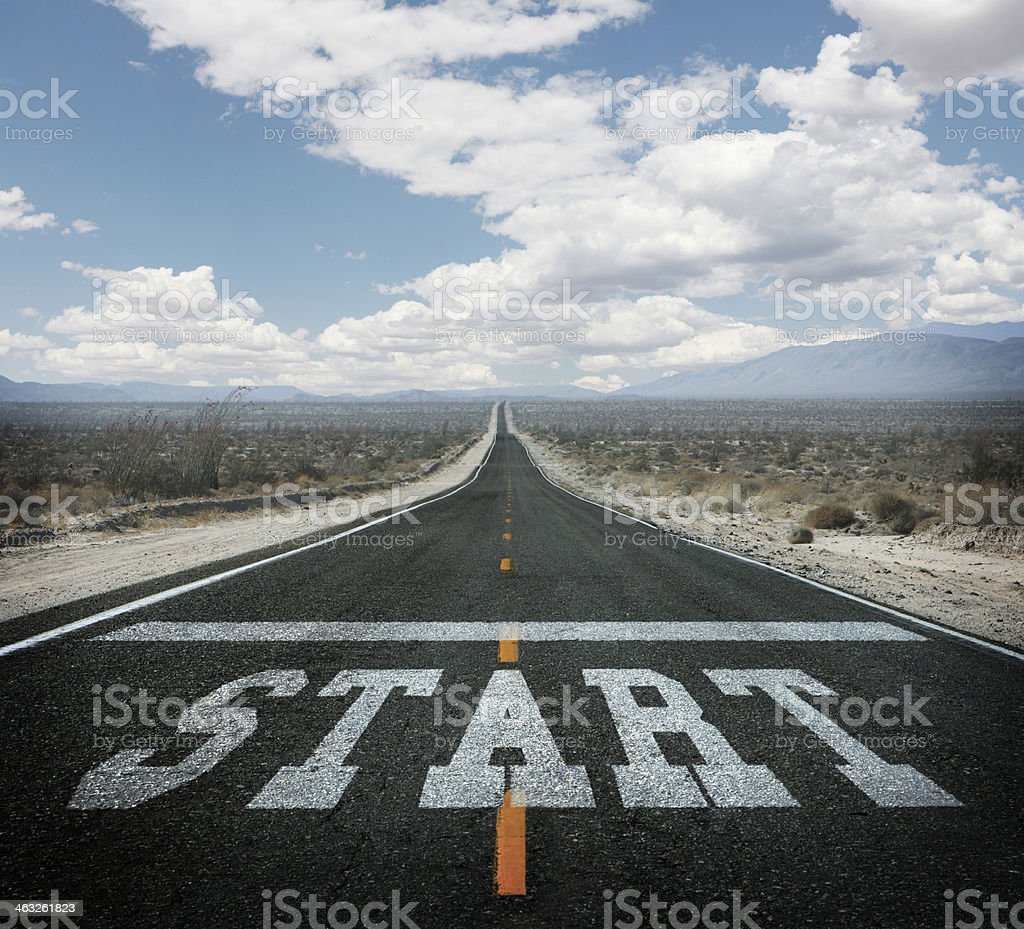 Starting line painted on long straight desert highway stock photo