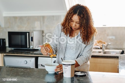 Cropped shot of a young woman making herself breakfast at home