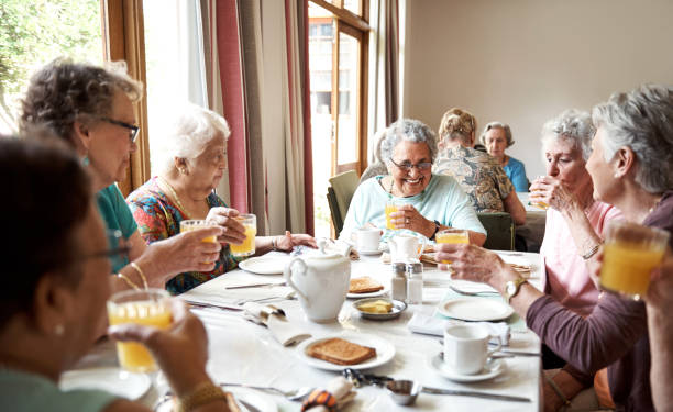 Starting their day the cheerful way Shot of a group of seniors enjoying breakfast together in their retirement home retirement community stock pictures, royalty-free photos & images
