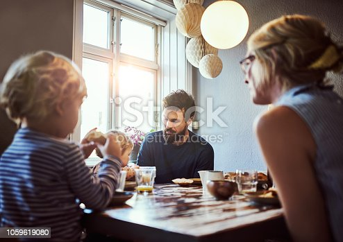 Cropped shot of an affectionate young family sitting down at the dining room table for breakfast