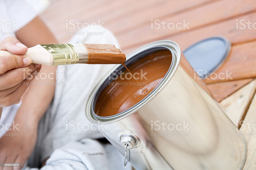 Starting to stain hardwood patio deck Paint brush and tin can used to stain hardwood Aluminum Stock Photo