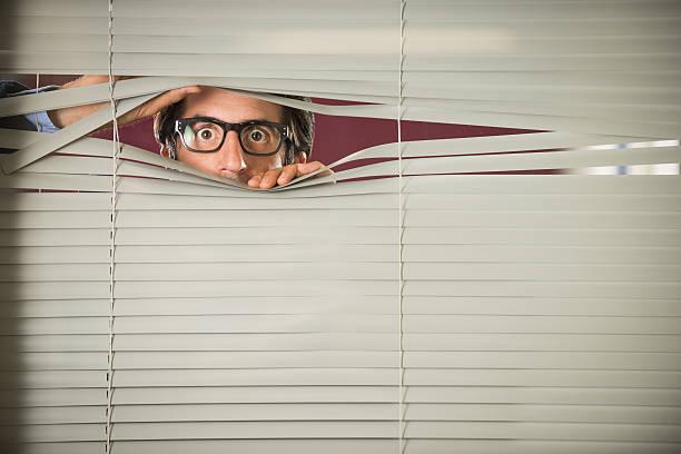 Startled Nerd staring Through Venetian Blinds stock photo