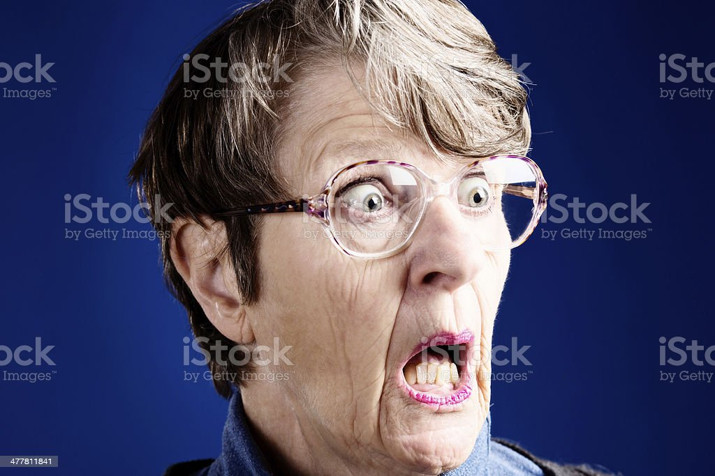 Startled, wide-eyed old woman gasps, looking to the side royalty-free stock photo