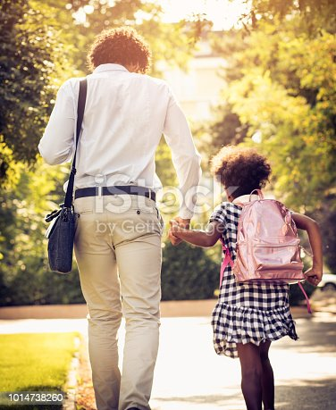 African American father and daughter running trough park.